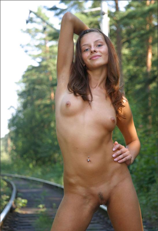 Красавица с пирсингом на животе гуляет по шпалам и раздевается 13 фото
