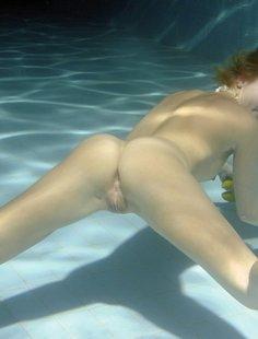 Рыжая пловчиха плавает под водой без одежды