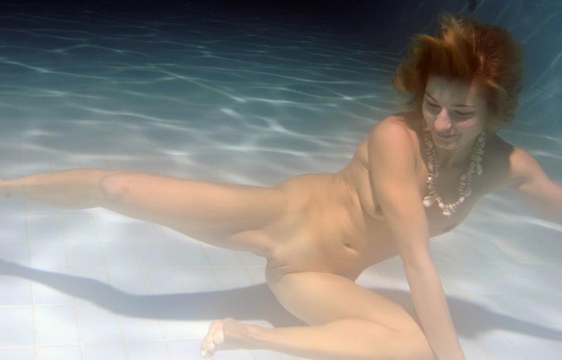 Рыжая пловчиха плавает под водой без одежды 4 фото