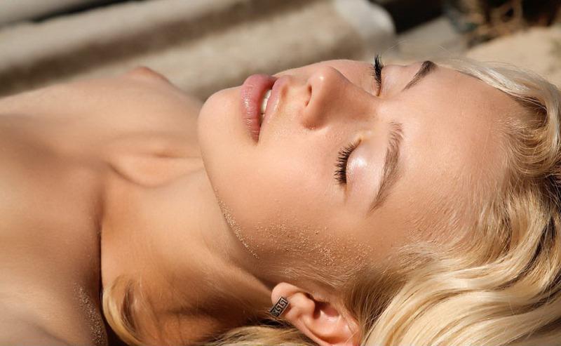 Худенькая блондинка онанирует киску на песочке 14 фото