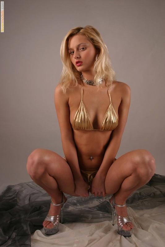 Худая блондинка в золотом бикини оголила бритую киску 7 фото