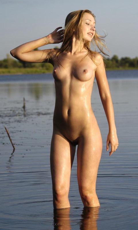 Блондинка с торчащими сосками позирует возле озера 8 фото