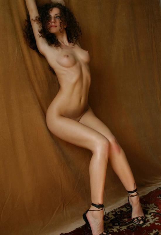 Парень снимает кудрявую худышку голышом на ковре у желтой шторы 15 фото