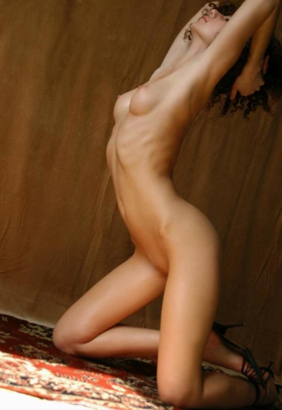 Парень снимает кудрявую худышку голышом на ковре у желтой шторы 13 фото