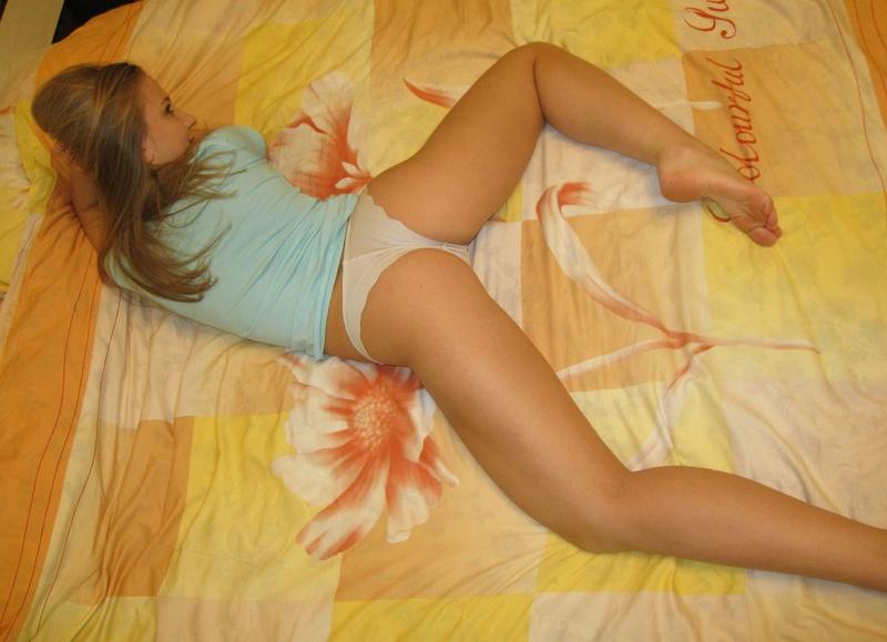 Молодая блондинка на кровати стягивает трусики и оголяет киску 5 фото