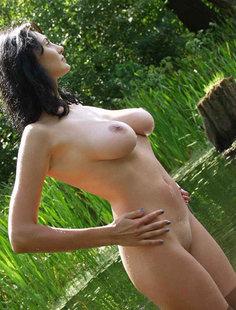 Грудастая брюнетка голышом купается в реке