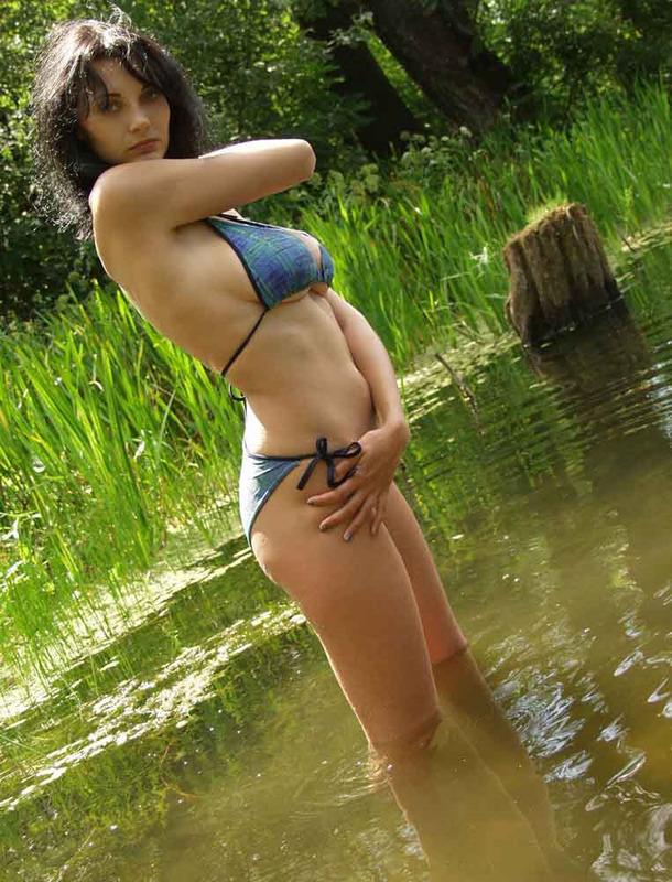 Грудастая брюнетка голышом купается в реке 2 фото