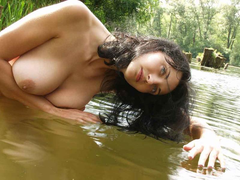 Грудастая брюнетка голышом купается в реке 9 фото