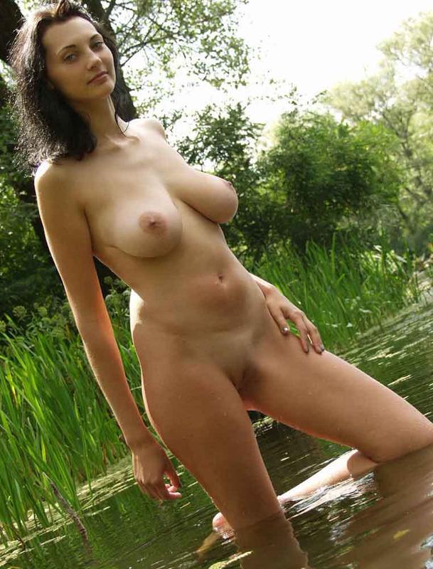 Грудастая брюнетка голышом купается в реке 12 фото