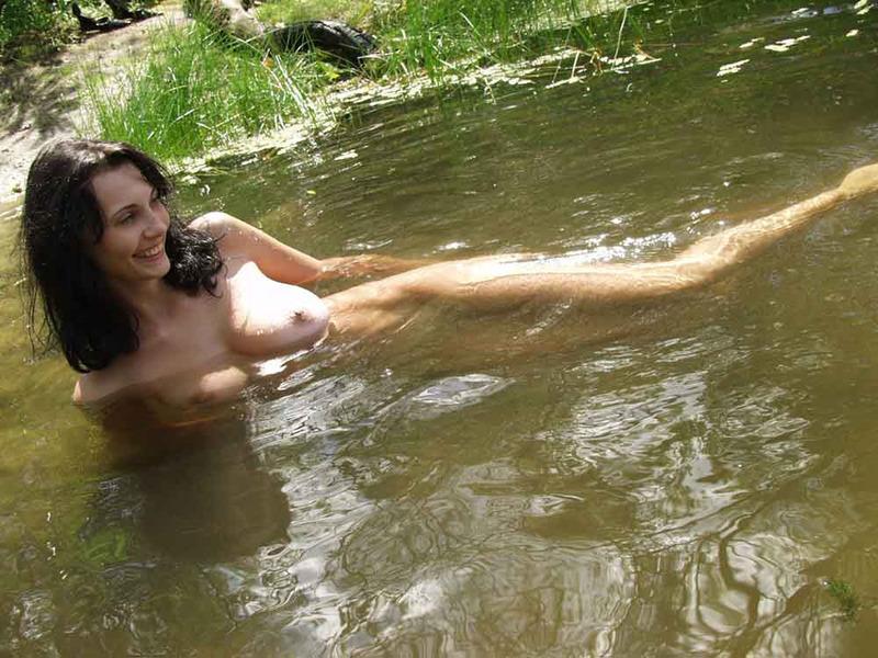 Грудастая брюнетка голышом купается в реке 14 фото