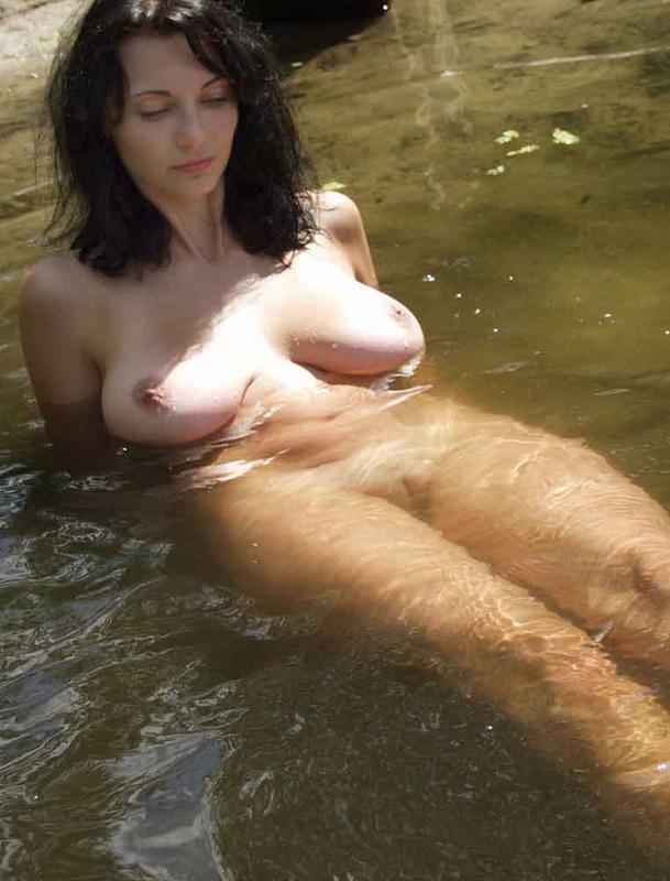Грудастая брюнетка голышом купается в реке 15 фото