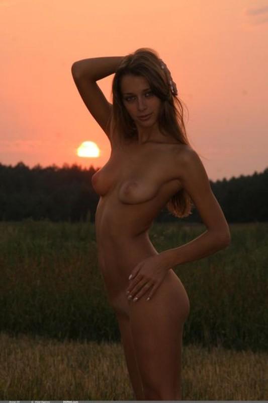 Голенькая нимфоманка позирует на закате в поле 27 фото