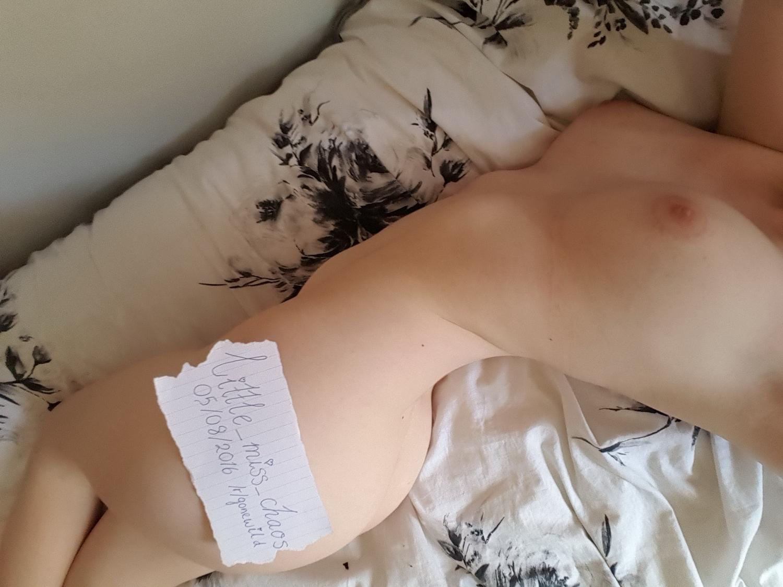 Милашка с запиской извивается голышом на кровати 4 фото
